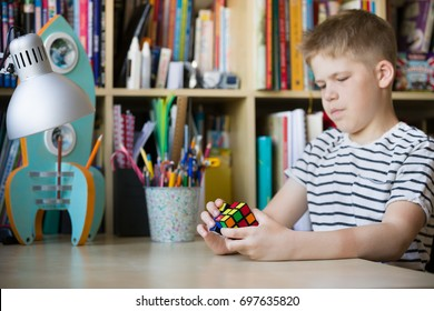 Moscow, Russia, August 16 2017: Portrait of cute kid boy holding Rubik's cube and playing with it at the desk in children room. Rubik's cube in child's hands.