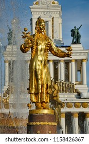 MOSCOW, RUSSIA - August 17, 2018 Golded Statue of Turkmenia in national costume holding a stem of cotton in Spray of Water Fountain of Friendship of Nations at VDNKh Exhibition