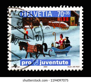 MOSCOW, RUSSIA - AUGUST 18, 2018: A stamp printed in Switzerland shows Holy Nicolas with his aid Schmutzli in a sledge, Pro Juventute: Children's Books - Children's World serie, circa 2000