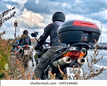 Moscow, Russia - August 18, 2019: Four motorcycle riders are on parking lot of Macdonalds waiting in line. Down low angle behind grass. In Moscow during motorcycle gymkhana competition