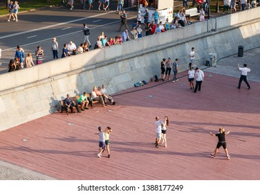 MOSCOW, RUSSIA - AUGUST 19, 2017: Unidentified couples having fun dancing at a recreational level in front of a small audiance at the Gorky park on a summer evening.