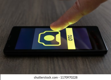 MOSCOW, RUSSIA - August 19, 2018: Smartphone on table displaying logo of 123RF OTG app. Finger above touch screen. Microstock photography On-the-Go. Direct shoot stock photo portfolio. Upload for sale