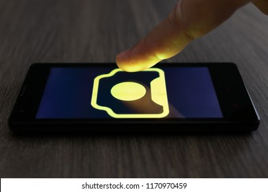 MOSCOW, RUSSIA - August 19, 2018: Smartphone on table displaying logo of 123RF app. Finger above touch screen. Microstock photography application for content creator. Direct buy and share stock photo.