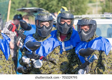 MOSCOW, RUSSIA - AUGUST, 2017: Paintball sport players in protective uniform and mask playing and shooting with gun outdoors