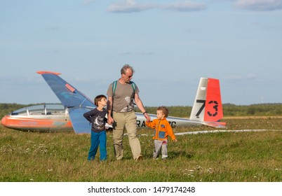 Moscow, Russia - August 2018: Pakhomovo glider training center. Pilot of glider after landing with his family. Boys happy to meet their father after his flight