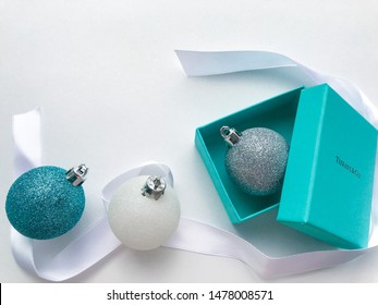 Moscow, Russia, August 2019: Close up of original box from the jewelry brand Tiffany and Co. with a silver Christmas ball inside, on the left - Christmas balls of white and blue, white ribbon around