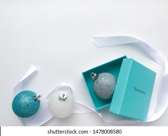 Moscow, Russia, August 2019: Original box from the jewelry brand Tiffany and Co. with a silver Christmas ball inside, on the left - Christmas balls of white and blue color and white ribbon around it