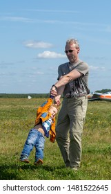 Moscow, Russia - August 2019: Pakhomovo glider training center. Pilot of glider after landing with his family. Boys happy to meet their father after his flight