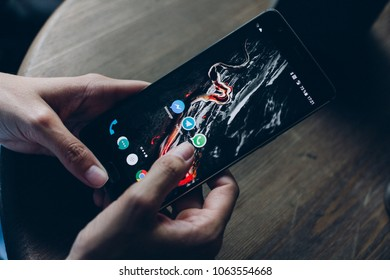 Moscow, RUSSIA - August 20th, 2017: Hands using smartphone One Plus 3T with icons of social media on screen. Smart phone life style, mobile phone era in everyday life.