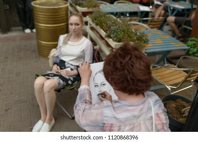 MOSCOW, RUSSIA - AUGUST 23, 2017: Artist draws a portrait of a young woman.