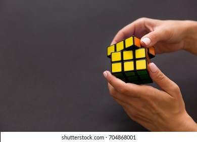 Moscow, Russia, August 24 2017: Rubik's cube in woman's hands, closeup, grey background. Girl holding Rubik's cube and playing with it.