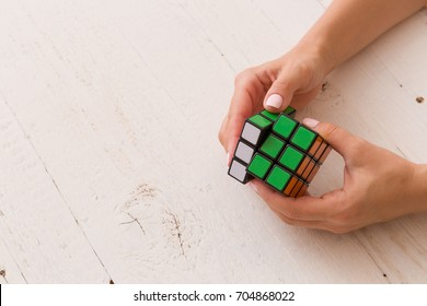 Moscow, Russia, August 24 2017: Rubik's cube in woman's hands, closeup, white wooden background. Girl holding Rubik's cube and playing with it.