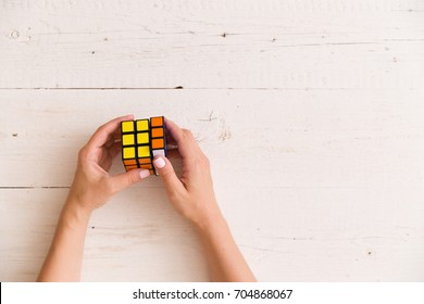 Moscow, Russia, August 24 2017: Rubik's cube in woman's hands, closeup, top view, white wooden background. Girl holding Rubik's cube and playing with it.