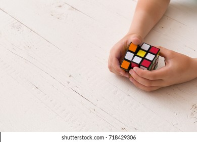 Moscow, Russia, August 24 2017: Rubik's cube in woman's hands, closeup, top view, white wooden background.. Girl holding Rubik's cube and playing with it.