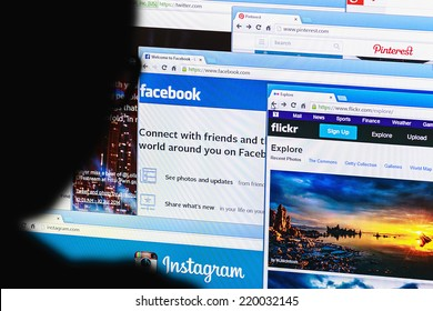 Moscow, Russia - August 26, 2014: Moscow,Russia - September 24, 2014:Close-up open pages of social networking on a home computer screen with silhouette of a man's head out of focus in the foreground.