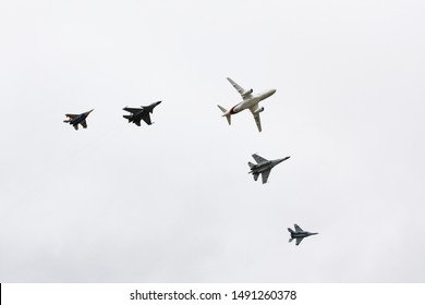 Moscow, Russia - August 30 2019: superjet SSJ 100 Accompanied SU-35, Mug-35, Su-30, Su-27 demonstrates the flight in airport Zhukovsky on salon MAKS 2019..