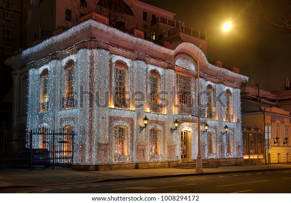 MOSCOW, RUSSIA - Beautiful Christmas lighting decoration of the 19th-century building of Cafe Pushkin covered with garlands as like a web made of hundreds of small light bulbs.