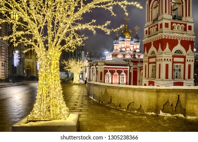 MOSCOW, RUSSIA - Beautiful colorful church of St. George with bell tower framed by illuminated new year artificial trees on Varvarka street in winter night.