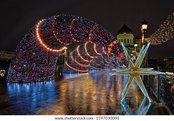 MOSCOW, RUSSIA - Beautiful and festive Christmas decorations in form of shooting stars of Bethlehem on Patriarchy Bridge in the background of Cathedral of Christ the Savior in early morning.