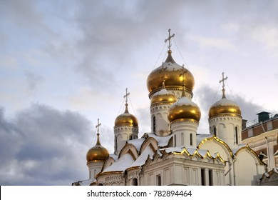 MOSCOW, RUSSIA - Beautiful onion-shaped gilded domes with crosses of Annunciation cathedral of Moscow Kremlin under grey skies in winter twilight.