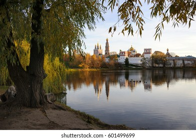 MOSCOW, RUSSIA - Beautiful view of Novodevichy convent framed with a tree at sunset with beautiful warm colors of the Golden Autumn season in the middle of October.
