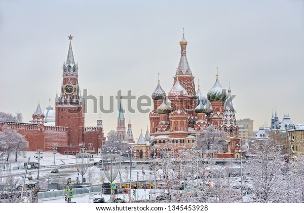 MOSCOW, RUSSIA - Beautiful winter cityscape with the view from Zaryadye park on the covered snow Spasskaya Tower (Savior's Tower) of Moscow Kremlin and St. Basil's Cathedral framed by white trees.