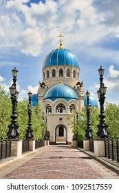 MOSCOW, RUSSIA - Byzantine Revival style Holy Vivifying Trinity Cathedral framed by ornate street lamps against blue sky with white clouds on a nice sunny spring day.