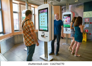MOSCOW, RUSSIA - CIRCA AUGUST, 2018: men use self ordering kiosk in McDonald's