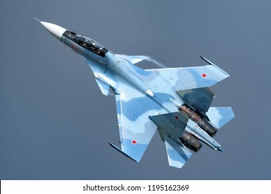 MOSCOW, RUSSIA - CIRCA AUGUST, 2018: russia air force twin jet engine Su-30SM Flanker fighter bomber jet aircraft fly aerobatic maneuver with dramatic stormy sky background close up detail aerial view