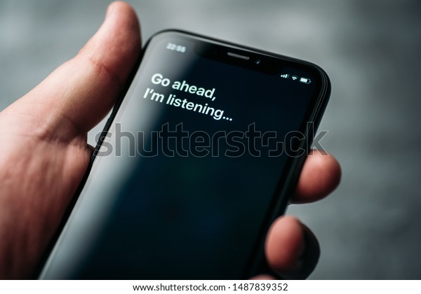 Moscow, Russia - Circa August 2019 : Iphone XR in male hand and activated by voice Apple digital assistant Siri and text on smartphone screen: Go ahead, I'm listening...