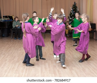 MOSCOW, RUSSIA - CIRCA DECEMBER, 2017: Open lesson of eurythmy. Waldorf school students of second class perform game exercise. Parents and guests in the background are watching.