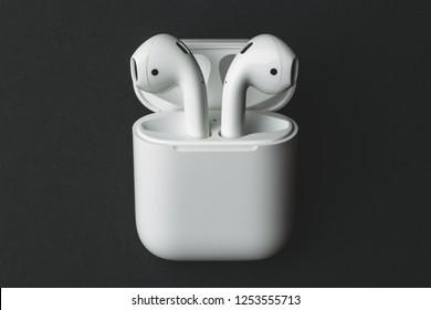 Moscow, Russia - Circa December 2018: Apple AirPods - wireless bluetooth earphones or headphones and white box for storage and charging, use with Iphone, Ipad or Mac