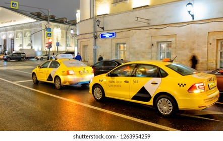 MOSCOW, RUSSIA - CIRCA DECEMBER, 2018: Moscow city historical street view of city taxi car in yellow and white color with logo of Yandex business technology internet online service company night view