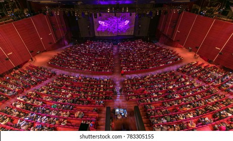 MOSCOW, RUSSIA - CIRCA FABRUARY 2017: Spectators gather in the auditorium and watch the show in theatre timelapse. Large hall with red armchairs seats. Viewers filling places until turn off the light