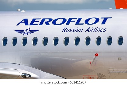 MOSCOW, RUSSIA - CIRCA JULY, 2017: Aeroflot Russian Airlines Sukhoi Superjet 100 twin jet engine passenger airplane side closeup fuselage view with aircraft windows logo lights landscape background