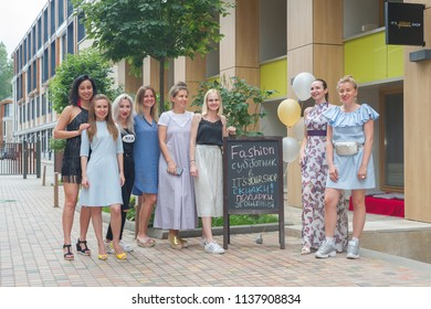 """MOSCOW, RUSSIA - CIRCA JULY, 2018: Group portrait. Employees of online store """"ItsYourShop.Ru"""" are posing for a memorable photo with advertising poster about discounts."""