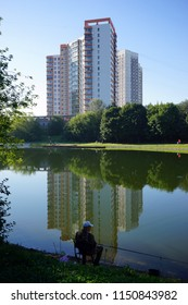 MOSCOW, RUSSIA - CIRCA JULY 2018 Apartment buildings and fisherman near Prazhskaya metro station