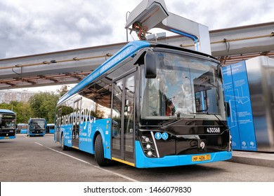 MOSCOW, RUSSIA - CIRCA JULY, 2019: Modern electric city bus of Moscow public transport system charging battery at charge station for hybrid vehicle on street of russian capital front wide view
