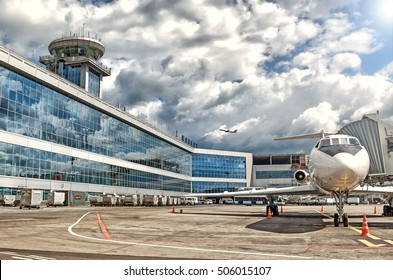 MOSCOW, RUSSIA - CIRCA MAY, 2011: Panoramic view of Moscow Domodedovo International airport terminal with air traffic control tower passenger airplane parked to gate jet way window reflection