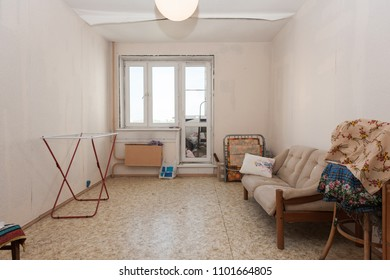 MOSCOW, RUSSIA - CIRCA MAY, 2018: A room in a two-room apartment. Wallpapers on ceiling get unstuck. Linoleum floor, window, door to loggia. Interior items, sofa.