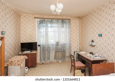 MOSCOW, RUSSIA - CIRCA MAY, 2018: A room in a two-room apartment. Wallpapers. Linoleum floor. Interior items, furniture. Window with curtain.