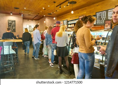 MOSCOW, RUSSIA - CIRCA OCTOBER, 2018: people staying in queue at counter service a Starbucks coffeeshop.