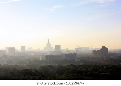 Moscow Russia city skyline in the mist. Forest in the foreground. Building shapes in the distance in the morning mist. High ground view. One of seven landmark buildings visible. Clear sky. Shilouette
