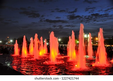 MOSCOW, RUSSIA - Colored Red Light Fountains in Victory Park Against Dusk Sky. Impressive water fountains illuminated with red spotlights during dusk in Victory Park on Poklonnaya Hill