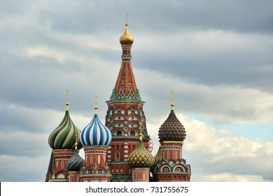 MOSCOW, RUSSIA - Cupolas of St. Basil's Cathedral Against Clouds. Beautiful colorful onion domes of St. Basil's Cathedral on Red Square against grey clouds.