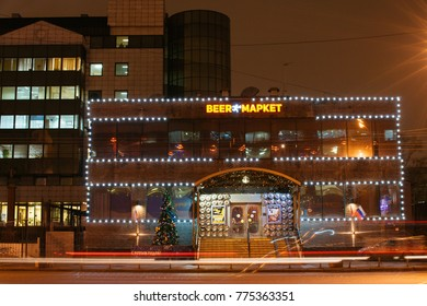 Moscow, Russia - Dec 12, 2017: Night view of the street with office building, shop, restaurant, beer market illuminated by lights of different colours