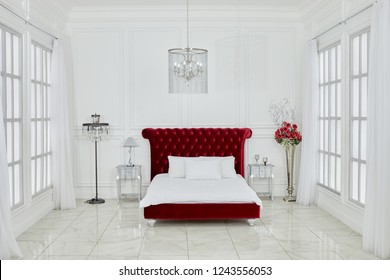 MOSCOW, RUSSIA - DEC 23, 2017: Interior of spacious white bedroom with large red bed, chandelier, lamps, flowers, windows on both sides in Ligtning Hall of Fotoelite Studio.