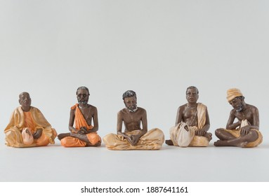 Moscow, Russia - Dec 25 2020: isolated figurines of yogi teachers in a row on white background. Art, figures, pray, concentration, faith, belief, hinduism, concentration, meditation, calm, peace