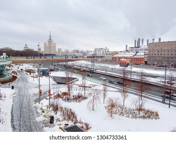 MOSCOW, RUSSIA - December 02, 2018. Zaryadye landscape urban park near Red Square. People walking among lawns under snow. River overlook - big bridge over Moscow-river.