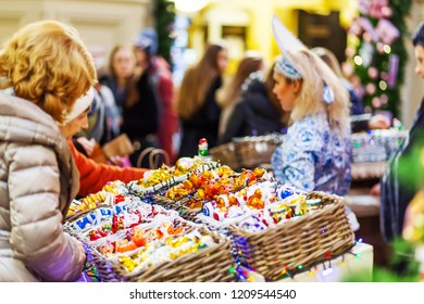 MOSCOW, RUSSIA - December 03, 2017. GUM (Main Department Store) decorated for New Year and Christmas fair. Sellers in national costumes. People buying old fashioned decorations.